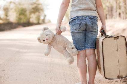 homeless child holding teddy bear and suitcase