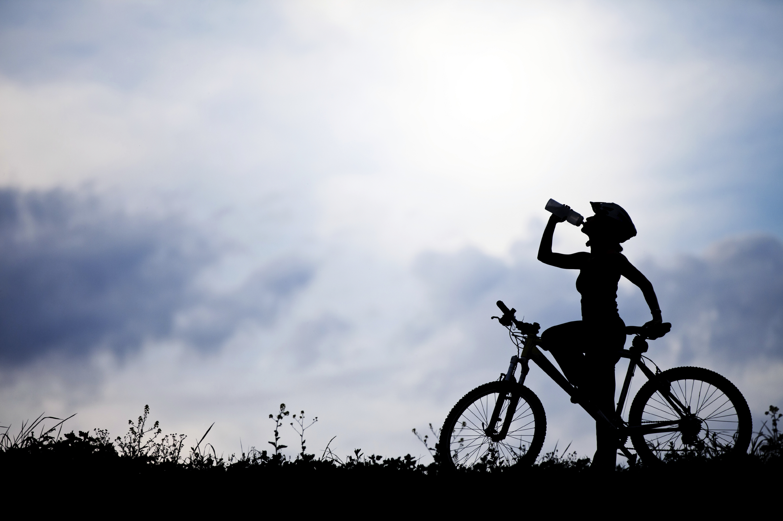 Image of woman riding bike stopping to drink water.