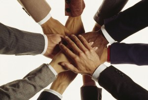 photo of hands in business attire joined making a circle