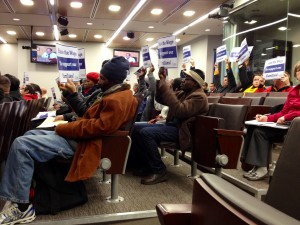 Workers hold up signs during the Montgomery County Council's vote to raise the minimum wage.
