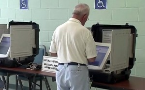 photo of man voting on touchscreen voting machine