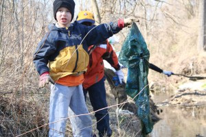 photo of boy cleaning up stream