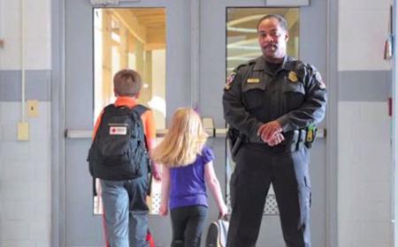 photo of school children and school resource office in school hallway