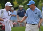 Caddie Erik Frost hands a golf  ball to Peter Hanson on the 1st green