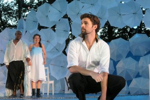 Photo of Prospero (Craig Wallace) and his daughter Miranda (Leah Filley) look on as Ferdinand (Alexander Korman) laments his father's fate in Olney Theatre Center's production of THE TEMPEST.