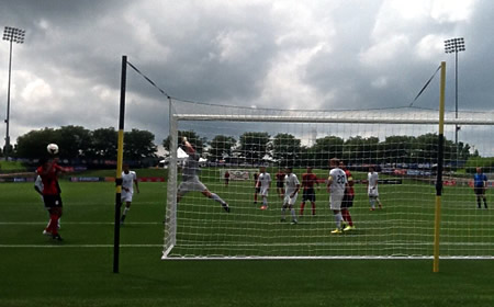 photo of youth soccer game from behind the goal net