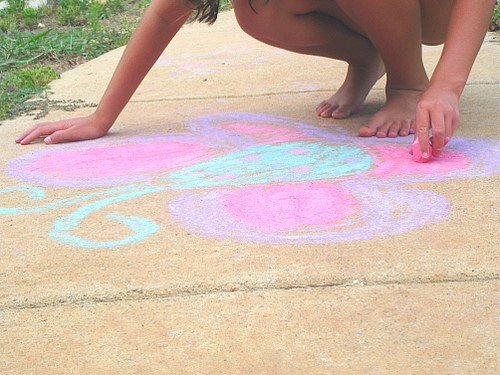 photo of child drawing on sidewalk with chalk