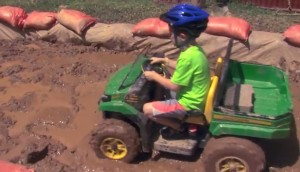 photo of young boy riding atv in mud pit at agricultural fair