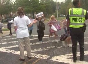 photo of school children crossing street with crossing guard