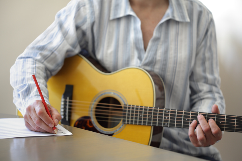 photo of Guitarist musician writing a song on his guitar