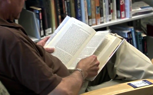 photo of man reading in library