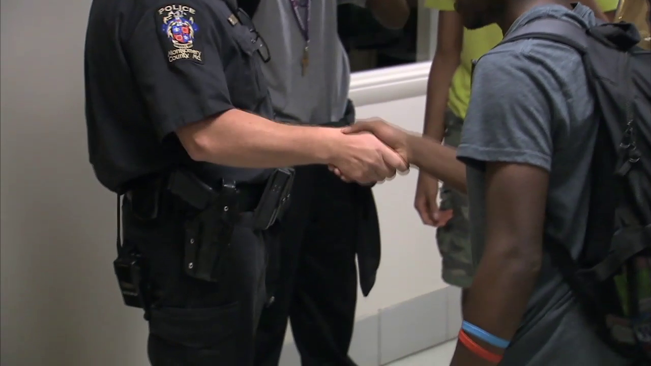 photo of school resource officer shaking hands with student