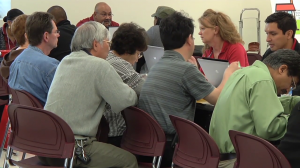 photo of people attending resource fair and getting assistance at a table