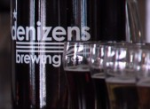 denizens brewing company bottle and glasses of beer