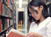 Woman reading in library stacks featured istock