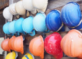 old colorful construction helmets on wood slat