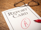 """Report card on an oak desk with a red """"A"""" written on it . A red pen in the foreground and glasses in the background."""