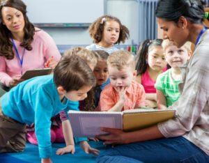 photo of teacher reading picture book to nursery school students