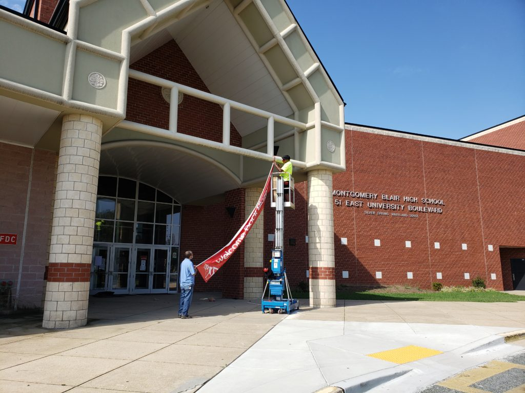 photo of bright welcome back blazers sign being hung on the front entrance