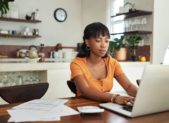 how-wfh-could-affect-taxes-young-woman-filing-taxes-at-home-1159809871