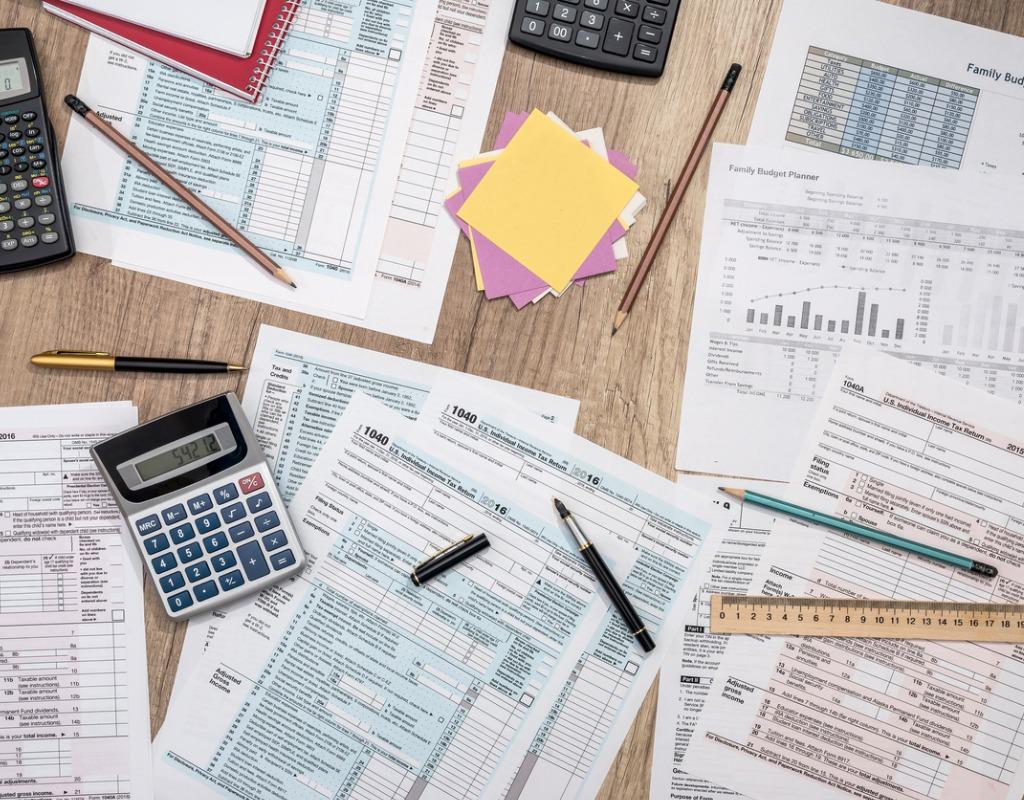 photo of saving concept tax form budget notepad-pen calculator