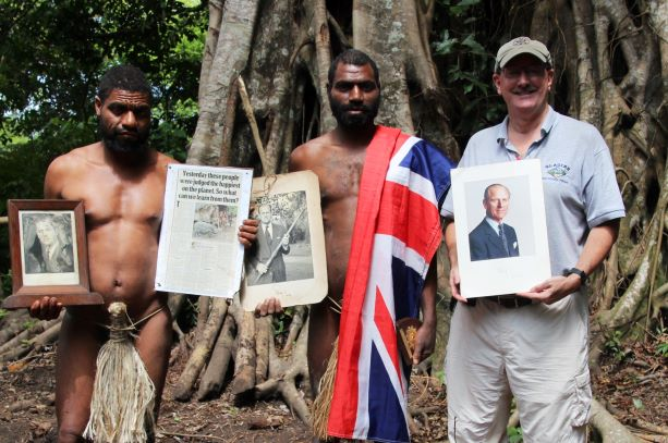 photo of Chief Linlin Jack Naiua, 27 years old, of Yaohnanen village on the island of Tanna in the South Pacific country of Vanuatu. He is holding a signed photo of Prince Philip with a pig-killing club/Toka dance stick from Tanna. Note the Chief's demure penis sheath.