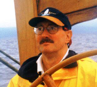 Lew at wheel of Soren Larsen